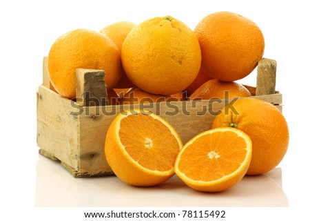 fresh oranges and two halves in a wooden box on a white background