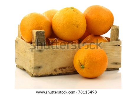 fresh oranges in a wooden box on a white background