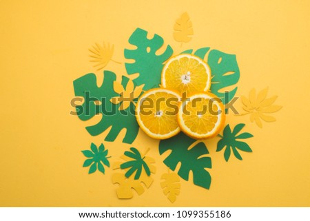 Fresh oranges with tropical leaves on a bright yellow background with copy space. Summer vacation flat lay with paper cutouts. #1099355186