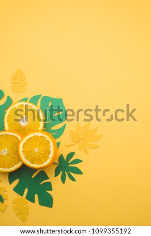 Fresh oranges with tropical leaves on a bright yellow background with copy space. Summer vacation flat lay with paper cutouts. #1099355192