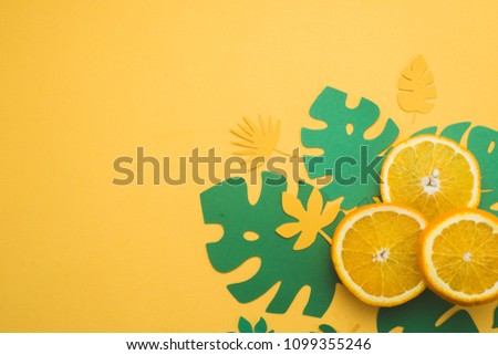 Fresh oranges with tropical leaves on a bright yellow background with copy space. Summer vacation flat lay with paper cutouts. #1099355246