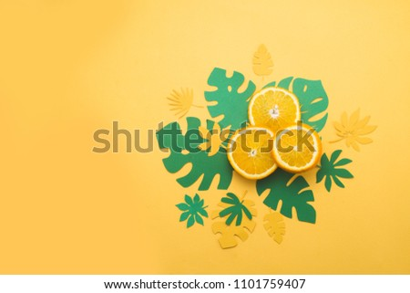Fresh oranges with tropical leaves on a bright yellow background with copy space. Summer vacation flat lay with paper cutouts. #1101759407