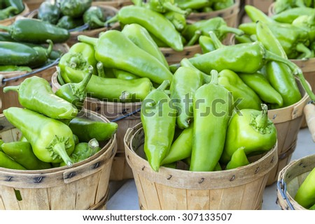 Fresh organic anaheim peppers in brown bushel baskets sitting on table at local farmers market