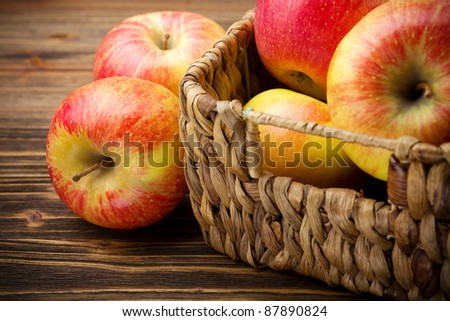 Fresh organic apples in basket on wooden table