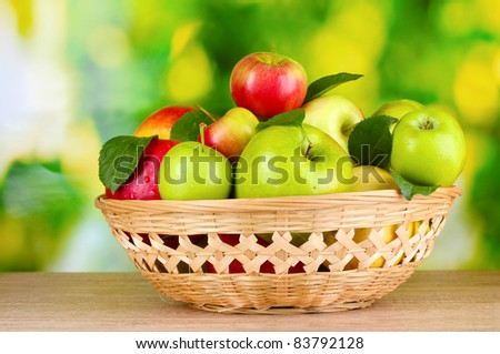 Fresh organic apples in basket on wooden table outside