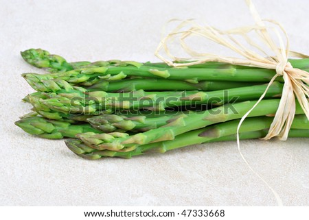 Fresh organic asparagus in a bunch tied with raffia on a tile counter top.  Selective focus on tips.  Copy space.