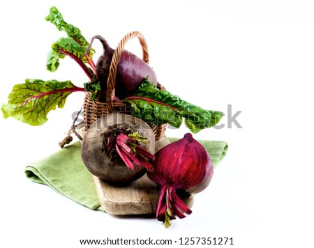 Fresh Organic Beet Roots with Green Beet Tops and One Half in Wicker Basket on Wooden Board and Napkin isolated on White background