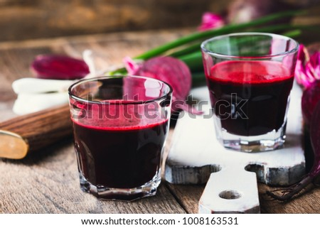 Fresh organic beetroot juice and fresh vegetables on rustic wooden table
