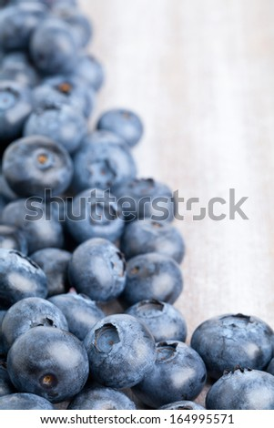 Fresh organic blueberries on white wooden kitchen table