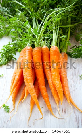 Fresh organic carrots on a wooden table - stock photo