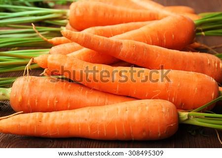 Fresh organic carrots on wooden table, closeup