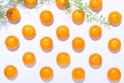 Fresh organic clementines in a geometric array on white background