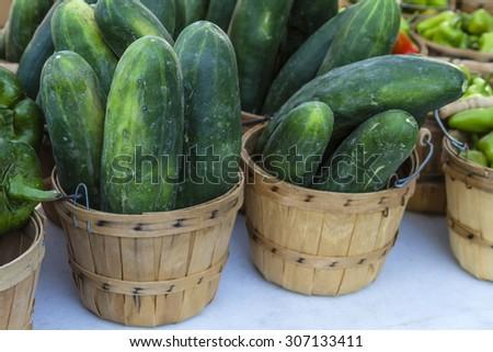 Fresh organic cucumbers in brown bushel baskets sitting on table at local farmers market