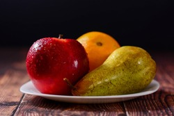 Fresh organic fruit red apple, orange and pear in white plate on rustic wooden table. glossy fruit with black background. Horizontal