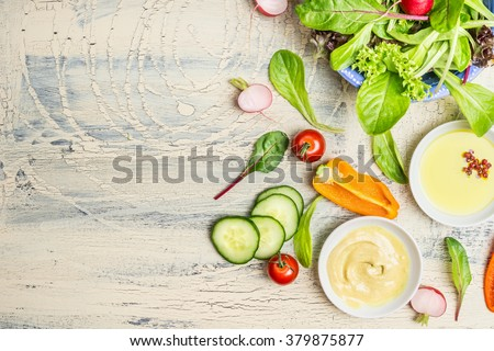 Fresh organic green salad preparation with oil and  dressing ingredients on light rustic background, top view, place for text. Healthy lifestyle or detox diet food concept #379875877