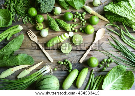 fresh organic green vegetables fork and spoon on wooden floor with copy space. concept Eat Healthy