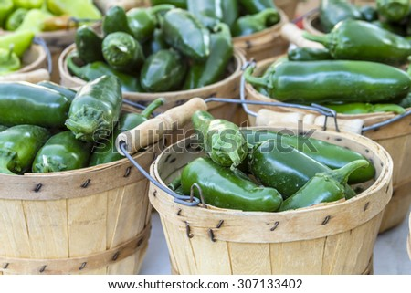 Fresh organic jalapeno peppers in brown bushel baskets sitting on table at local farmers market