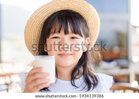 Fresh organic lactose free milk on glass.Asian cute little girl drinking milk.Calcium vitamin from milk.Grocery food.Good taste.Kid drink goat milk.School kid girl wearing straw hat.Delicious tasty.