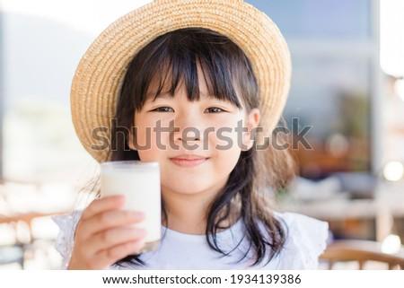 Fresh organic lactose free milk on glass.Asian cute little girl drinking milk.Calcium vitamin from milk.Grocery food.Good taste.Kid drink goat milk.School kid girl wearing straw hat.Delicious tasty.