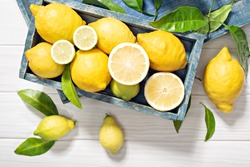 Fresh  organic lemon fruits with leaves on wooden table. Healthy food concept. Vitamin C