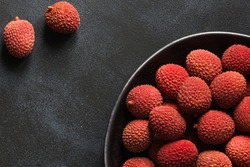 Fresh organic Lychee (Litchi fruit) in black plate on dark background. Close up. Copy space. Flat lay, top view.