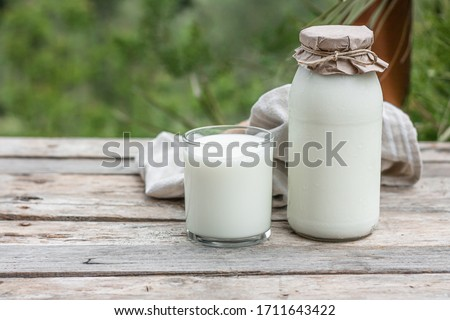Fresh organic milk in glass and bottle on rustic wooden table on nature background. Vegetable milk, vegan milk, Kefir, or Turkish Ayran drink for helthy eating. Space for text