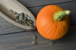 Fresh organic orange pumpkin with dry styrian pumpkin seeds on wooden plate over dark old wooden table background, top view.