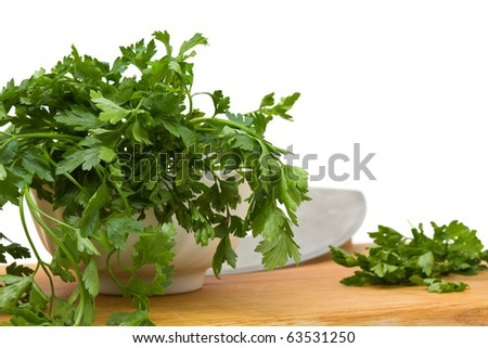 Fresh organic parsley in bowl over white background