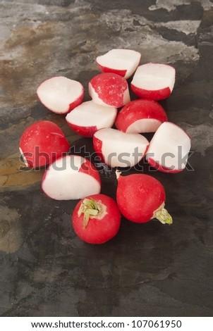 Fresh organic radish against grey slate - stock photo