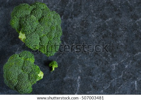 Fresh, organic raw broccoli on black background