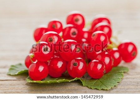 Fresh organic red currants on wooden table