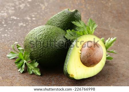 fresh organic ripe avocado with leaves of parsley