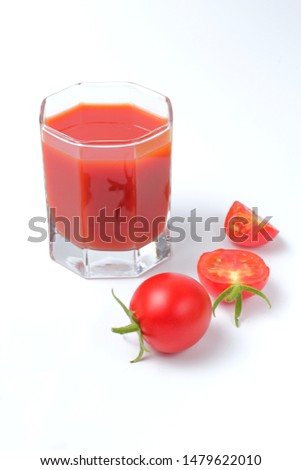 Fresh organic tomatoes, a glass of freshly squeezed tomato juice, a white background, bright natural color.