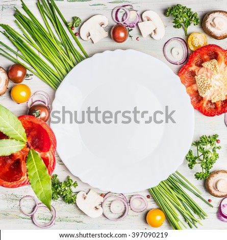 Fresh organic vegetables and seasoning ingredients for tasty vegetarian cooking around blank white plate , top view. Healthy or diet food concept.