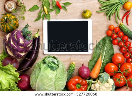 Fresh organic vegetables on a wooden background and digital touch screen tablet. Fresh vegetables background. Diet. Dieting. Space for your text.