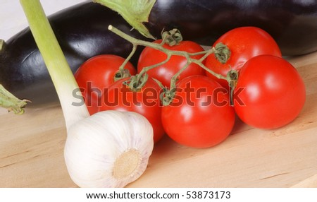 Fresh, organic vegetables on a wooden cutting board: eggplants, garlic and tomatoes. Studio shot