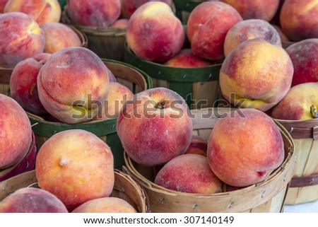 Fresh organic yellow peaches in brown bushel baskets for sale at local farmers market
