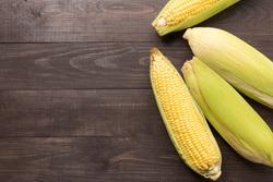 Fresh organic yellow sweet corn on wooden table. Top view.