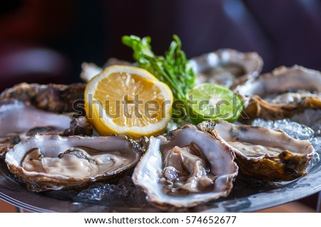 Fresh oyster in dish with lemon and lime  #574652677