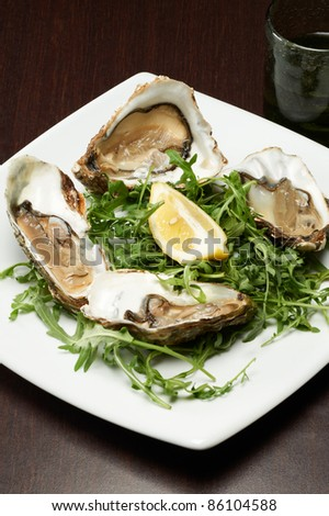 fresh oyster seafood served with lemon and arugula