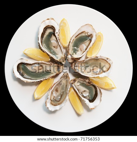 Fresh oysters on plate with lemon isolated on black background
