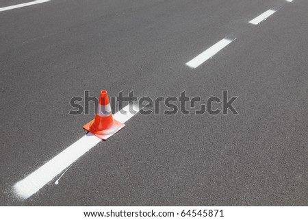 Fresh painted line at asphalt road and traffic cone