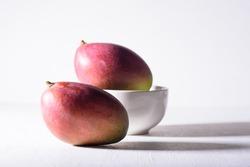 Fresh palmer mango fruit in a bowl on white background, Tropical fruit