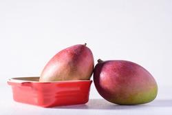 Fresh palmer mango fruit in red bowl on white background, Tropical fruit