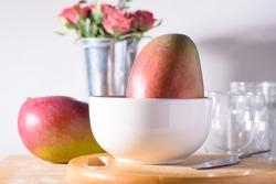Fresh palmer mango fruit in white bowl on white background, Tropical fruit