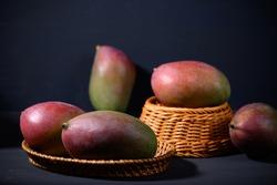Fresh palmer mango in a basket on black background, Tropical fruit