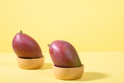 Fresh palmer mango in a bowl on yellow background, Tropical fruit