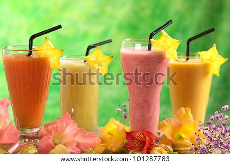 Fresh papaya, strawberry, pineapple and mango fruit juices and milkshakes with straws decorated with flowers (Selective Focus, Focus on the papaya and strawberry juices in the front)