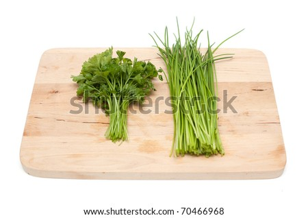 fresh parsley and chives on wooden board isolated