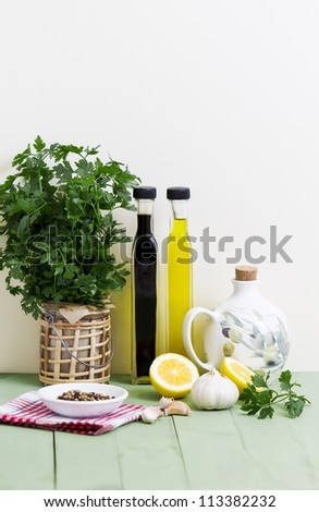 Fresh parsley, garlic, balsamic vinegar, olive oil, peppercorns and lemon on a table.